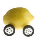 Lemon on car wheels to depict lemon law concept