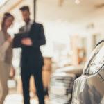 Woman talking to car salesman at dealership