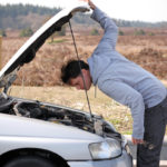 Man looking inside a salvage vehicle