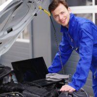 Mechaniker arbeitet mit einem Laptop an einem Auto, Motorsteuerung