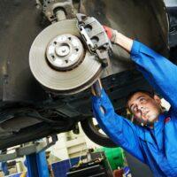 auto mechanic at car brake shoes examining