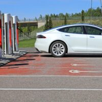 White Tesla Model S Electric Car Charging Battery at Tesla Supercharger station, side view.