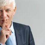 Business Lifestyle. Businessman standing isolated on gray showing secret gesture looking camera playful close-up