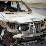 A car after a fire, close-up. A blown-up and burnt-out SUV on a city street. Criminal showdowns of gang groups.