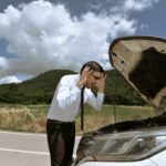 A young business man strained with his damaged car, looking frustrated at the engine failure.