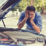 stressed man with broken car looking at failed engine